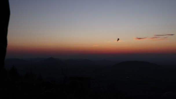 Mladý muž triumfálně skočil na počest dobytí vrcholku hory v Beskydech při západu slunce. Svoboda. Van Life. Pěší turisté mají výhled. Frolicsome na pahýlu. Nádherná barevná obloha