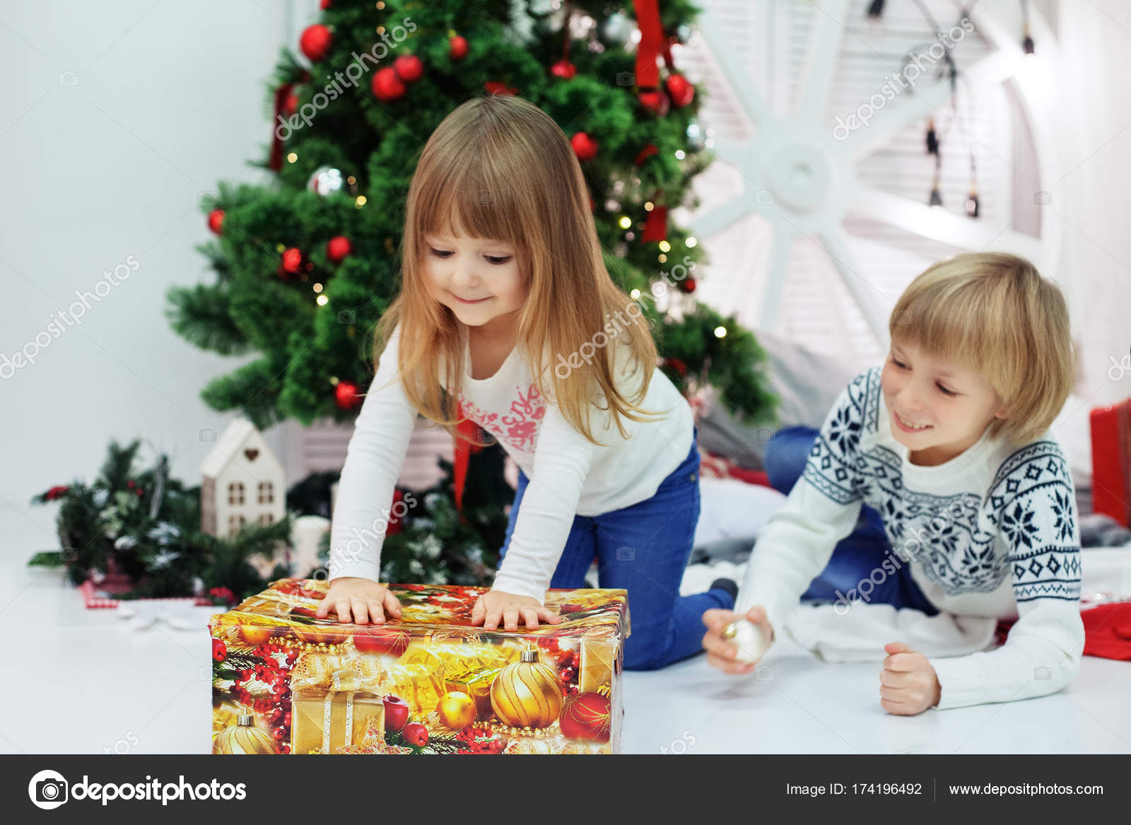 little brother and sister unpack gifts the concept of christmas stock photo