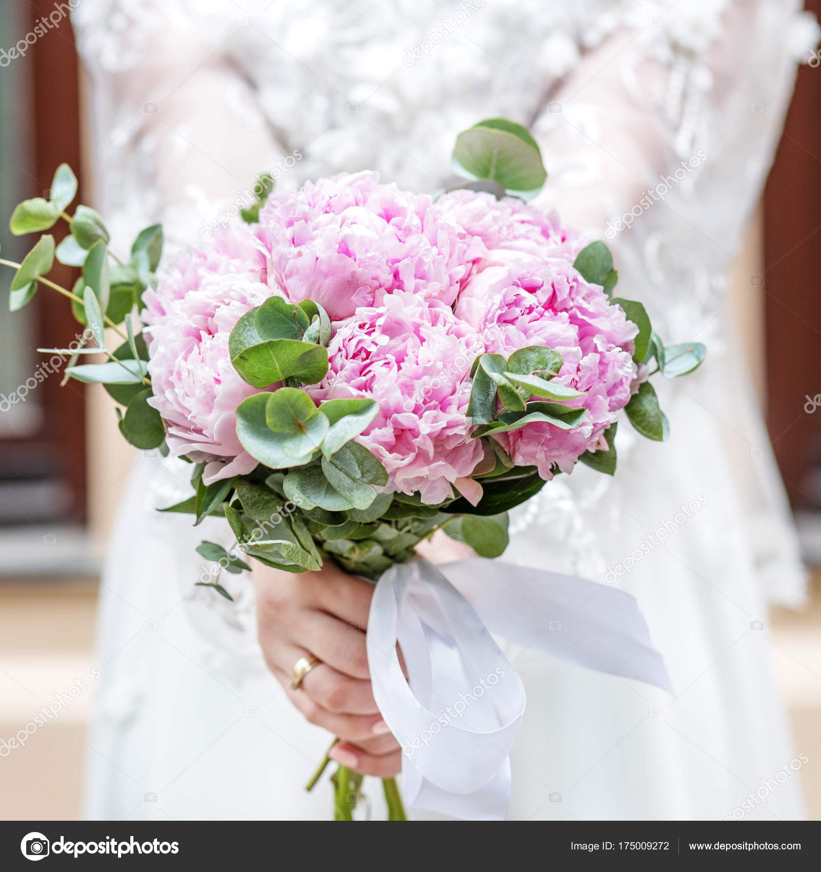 Wedding bouquet of flowers of pink peony in the hands of the bri ...