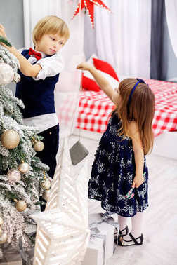 Little brother and sister decorates a Christmas tree in the room