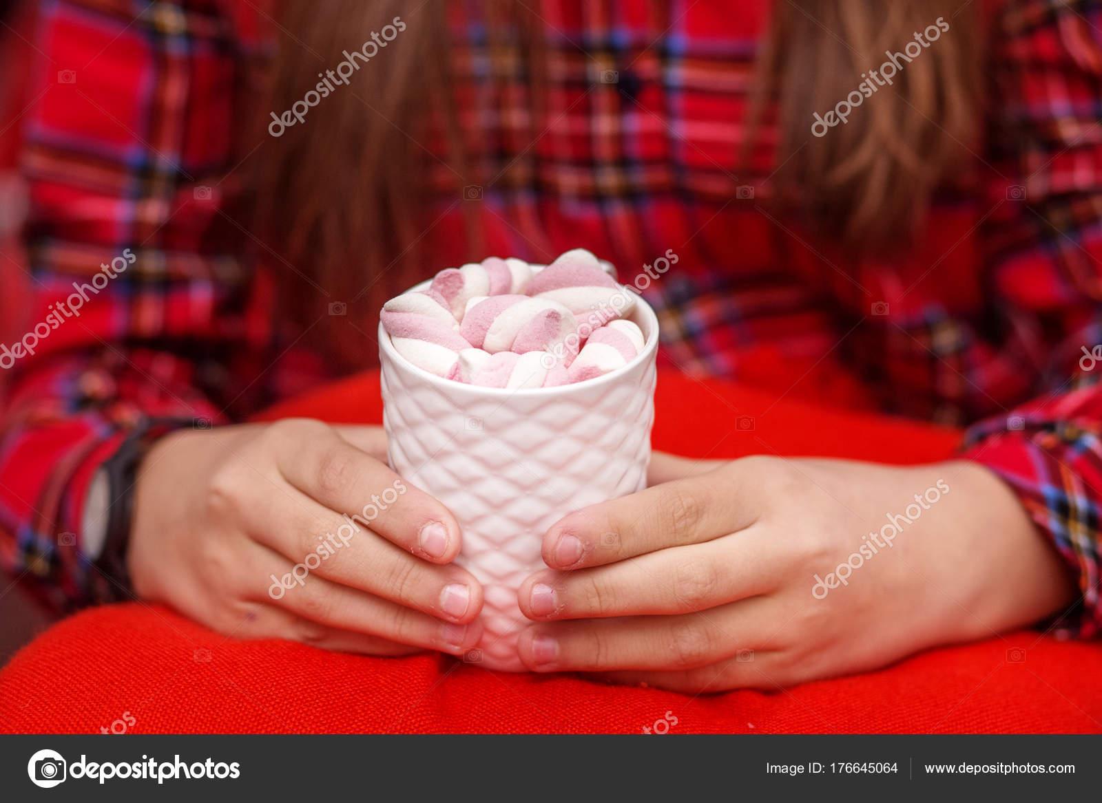 Weibliche Hände halten heiße Tasse Kakao oder Kaffee mit Farbe marsh ...