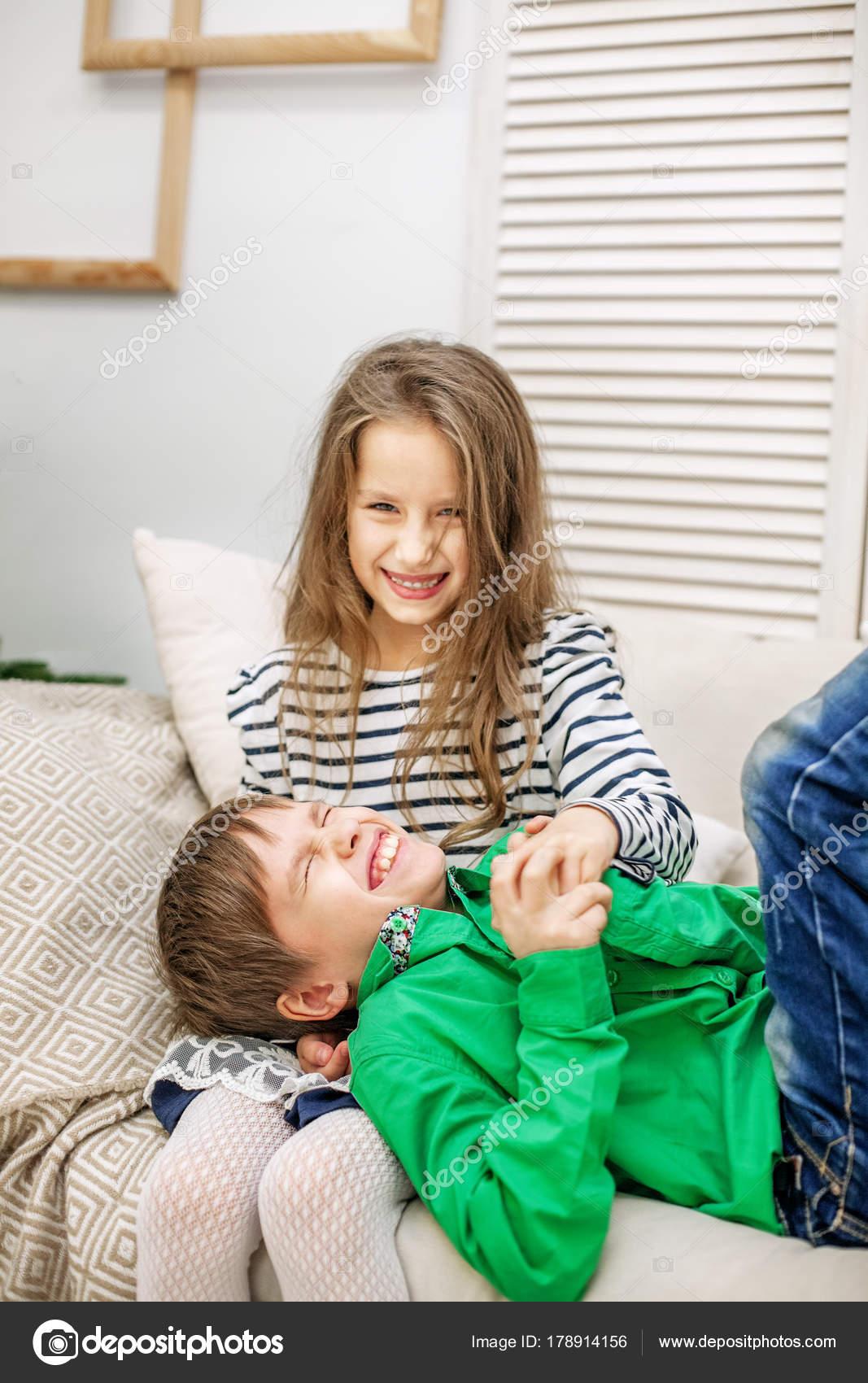 372ec918307 Δύο παιδιά καλπάζει στον καναπέ. Το αγόρι και το κορίτσι ...