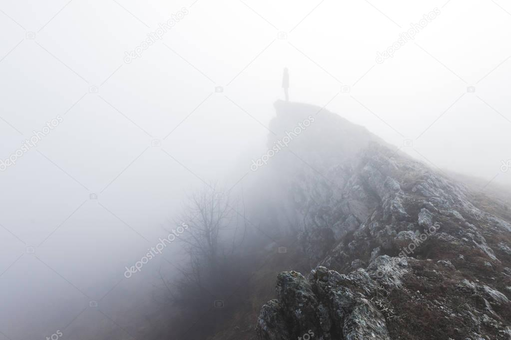 Man standing alone in the fog