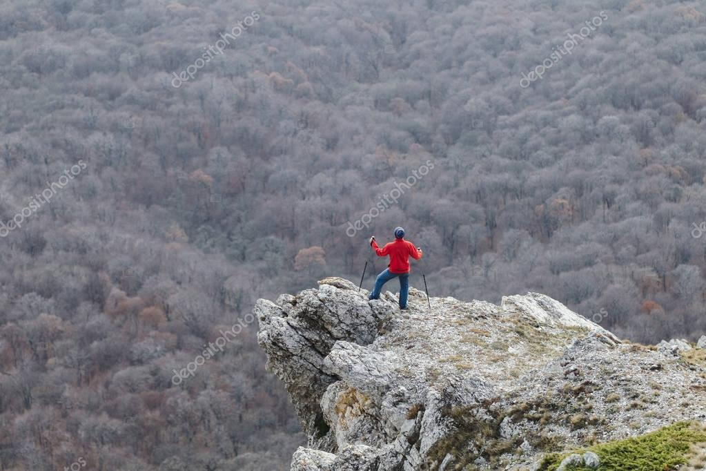 Man climbing to the edge of rock