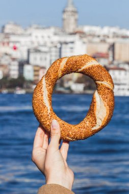hand holding a traditional Turkish simit