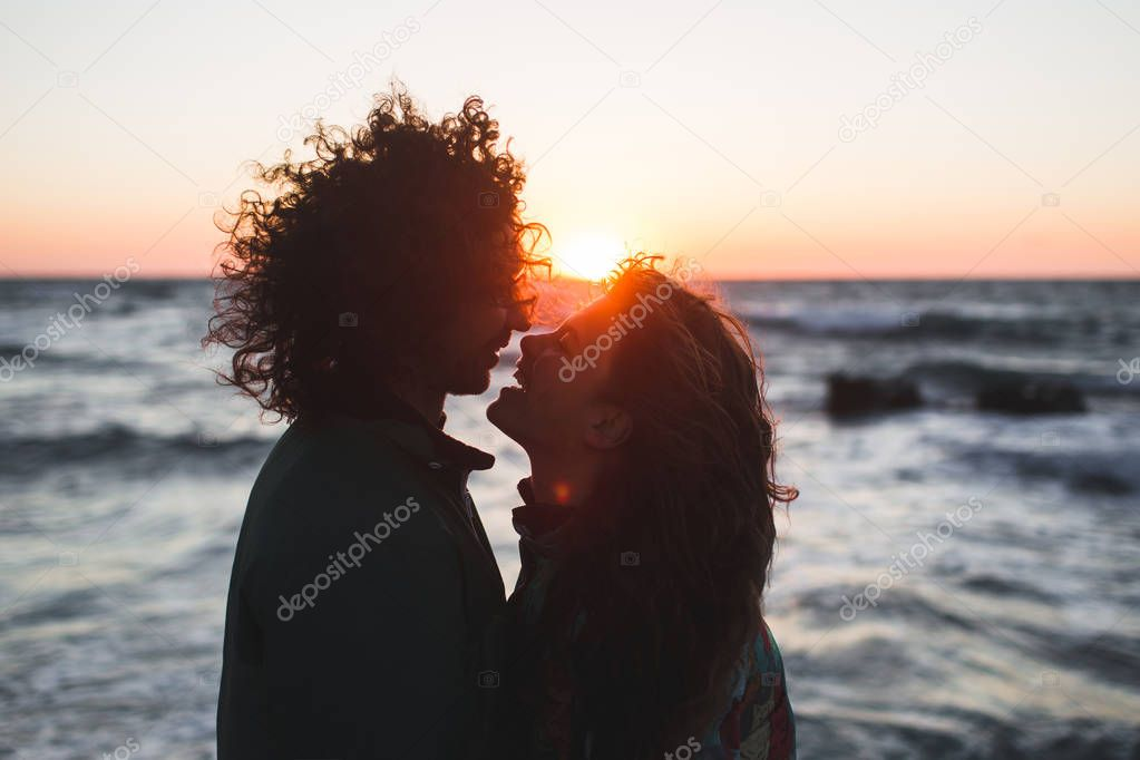 hipster couple  kissing at sunset.