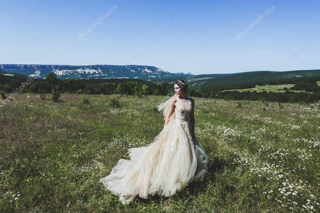 Portrait of fashion bride in green field