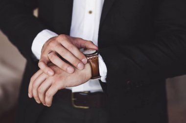 Man in black suit wearing new watch