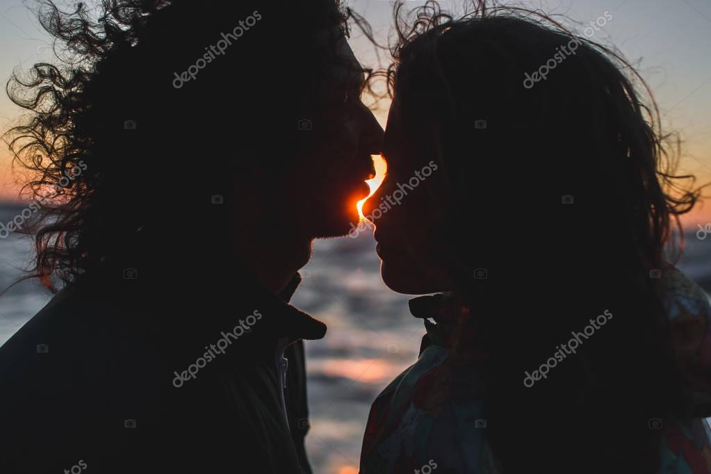 Young hipster couple  kissing at sunset.