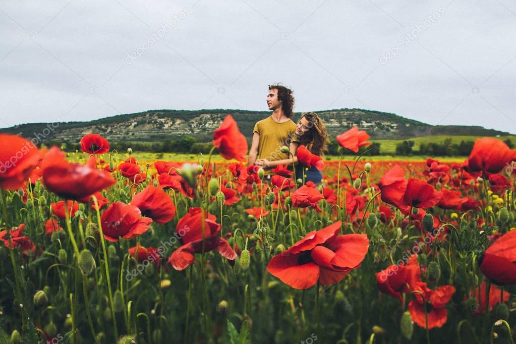 Young happy couple in blossoming field