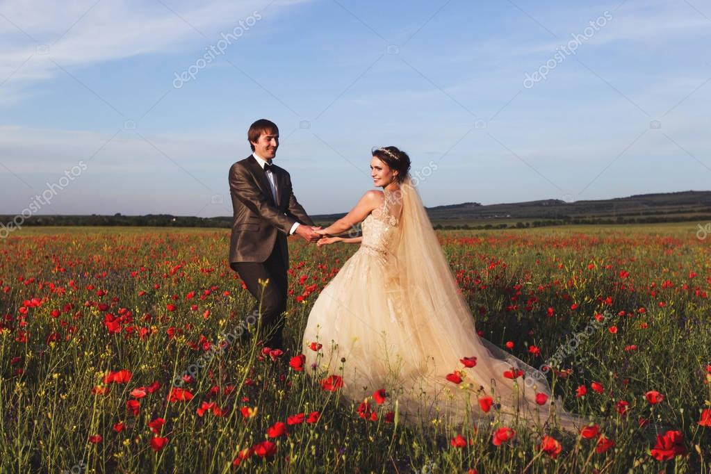Newlyweds walking in amazing blossoming flowers