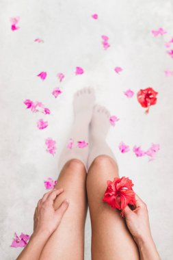 Woman relaxing in bath with tropical flowers