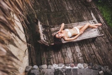 Woman relaxing on wooden chaise lounge