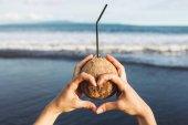 Photo Woman holding coconut at ocean coast
