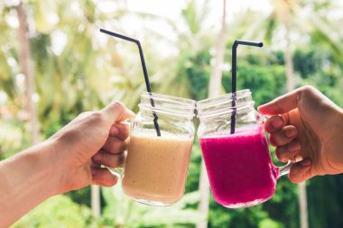 Two colorful fruit shakes in hands