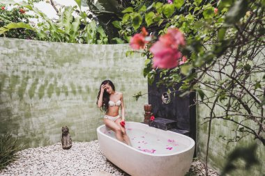 Woman relaxing in round outdoor bath
