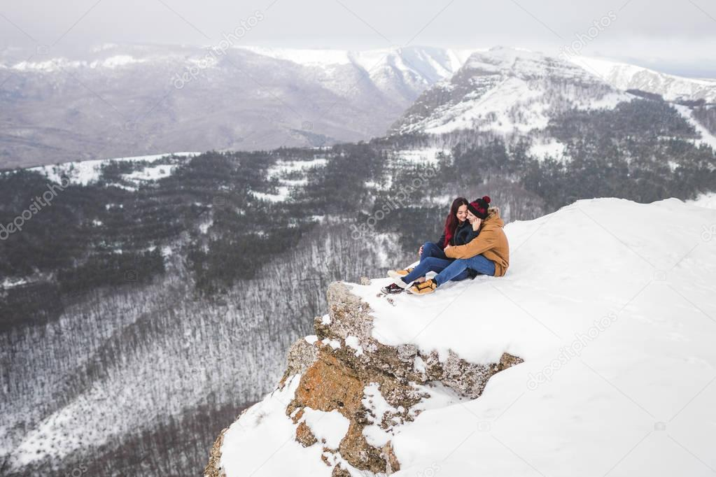 Couple sitting on edge of cliff in mountains