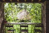 Bar pult a třemi židlemi s výhledem do zahrady v Bali