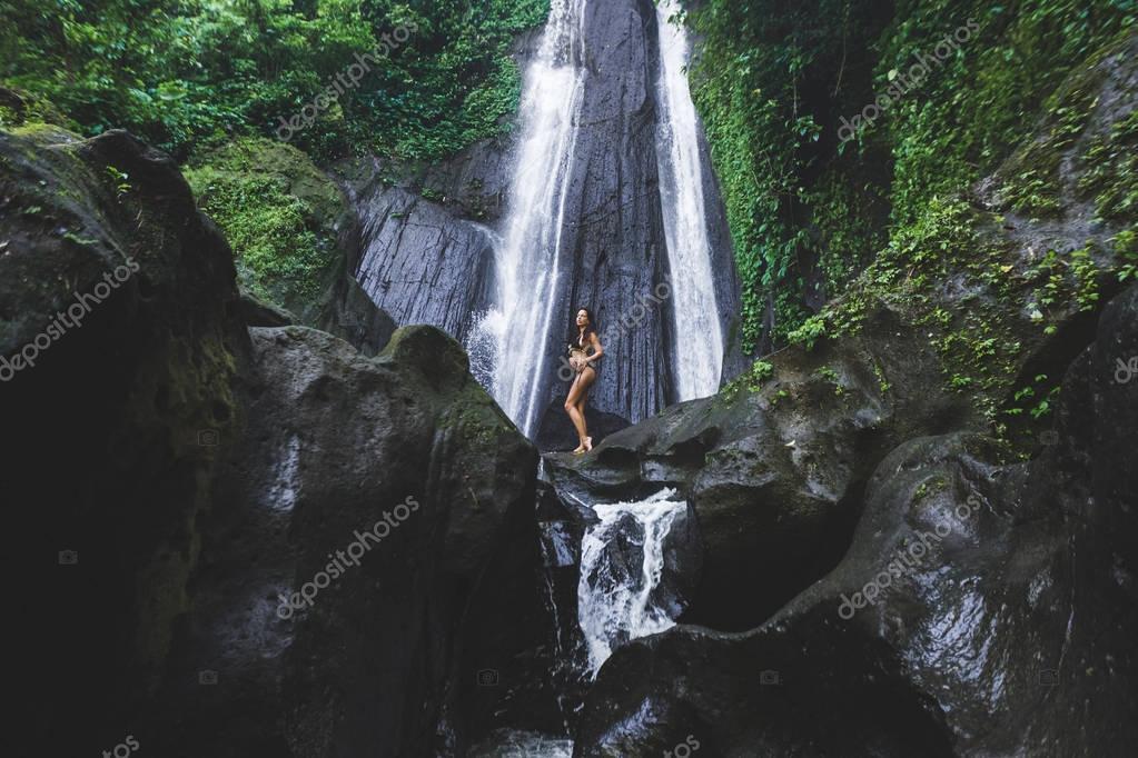 Woman enjoying near hidden in jungle cascade waterfall in Bali. Slim body and black swimsuit, fashion model. Dusun Kuning in Ubud area