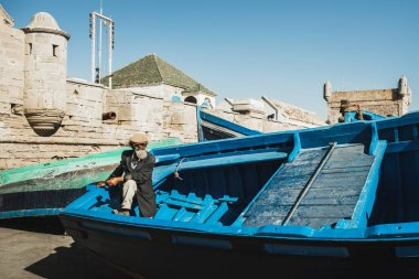 ESSAOUIRA, MOROCCO - SEPTEMBER 10, 2019: Old senior fisherman on blue wooden boat in Essaouira harbour. Stylish look, hat, beard, sunglasses and jacket. Moroccan people.