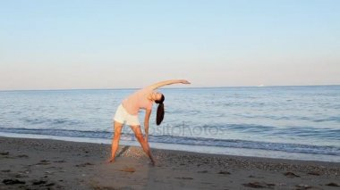 Girl goes in for sports on the beach by the sea