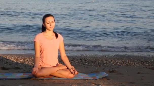 das Mädchen ist mit Yoga-Strand Meer beschäftigt