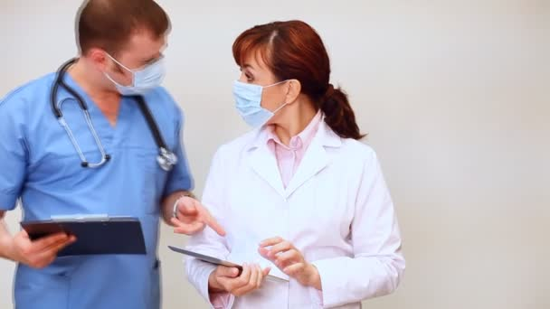 Arzt mit Stethoskop berät Krankenschwester im Krankenhaus mit Tablette