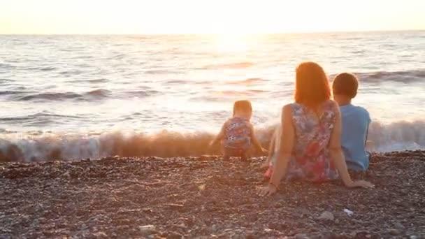maminka s dvěma kluky, synové odpočinku na pláži u moře při západu slunce,