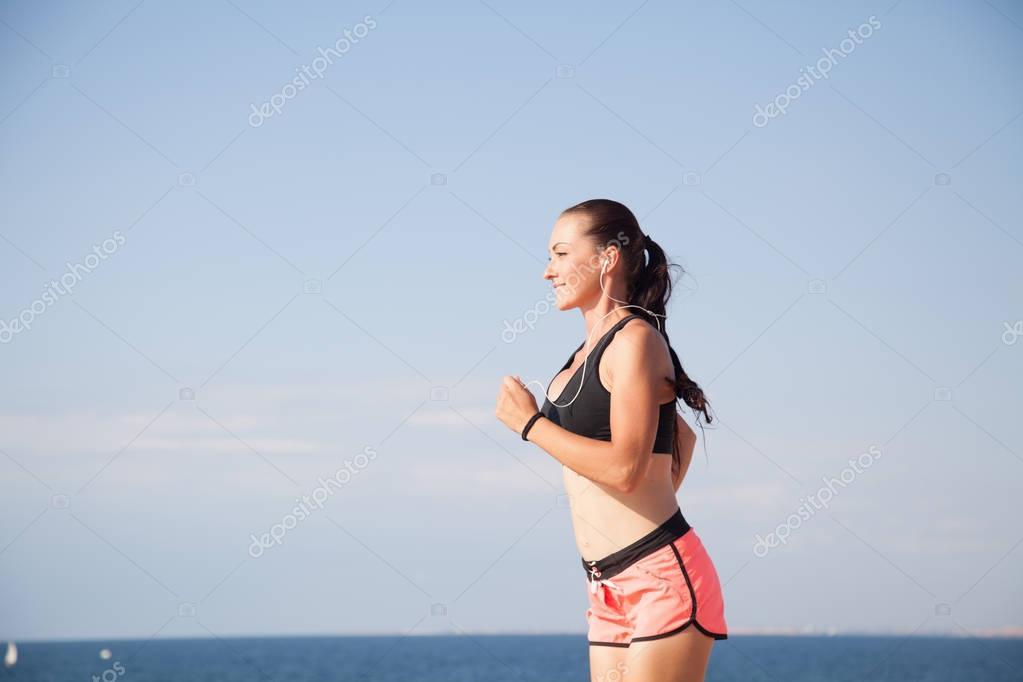 woman on the run sports runs on the beach listening to music