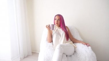 The girl with the pink hair is sitting in a white armchair drinking coffee or tea