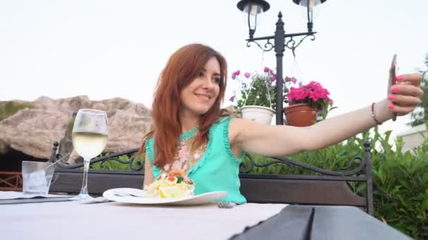 žena bere svoje fotky na svém smartphonu v restauraci