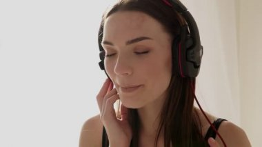 girl in large headphones listening to music in the bedroom