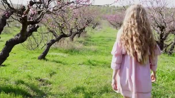 in the garden of flowering trees goes blonde girl in pink dress