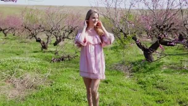szőke nő, rózsaszín ruha, őszibarack fák virágzó kerttel