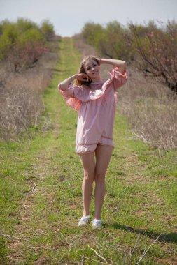 """Картина, постер, плакат, фотообои """"блондинка в розовом платье гуляет по цветущий сад весной"""", артикул 193995838"""