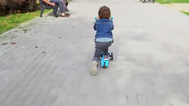 Child riding scooter on green kick board.