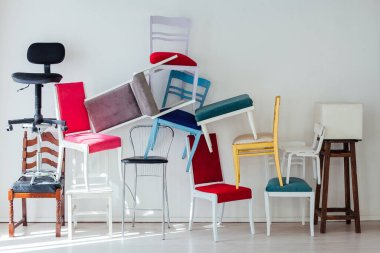 many multicolored chairs stand against the wall of the interior of the white room