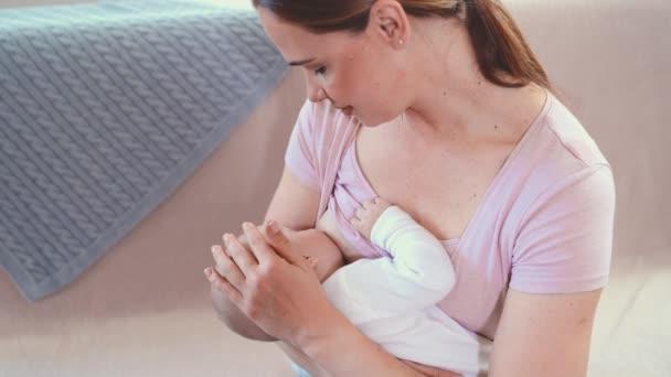 Mutter füttert Baby zu Hause. Stillende Mutter mit kleinem Kind