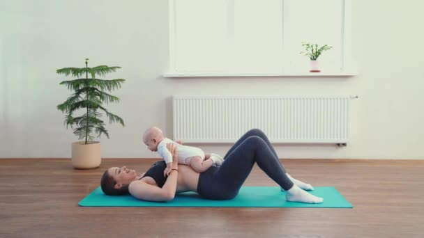 Mom does fitness with the baby at home