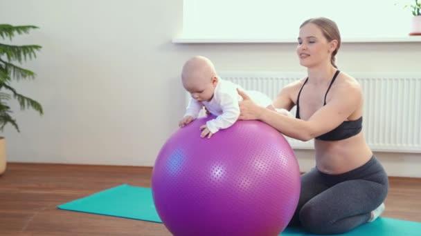 fröhliche Mutter spielt mit Säugling, macht Baby-Fitnessübungen auf großem Ball