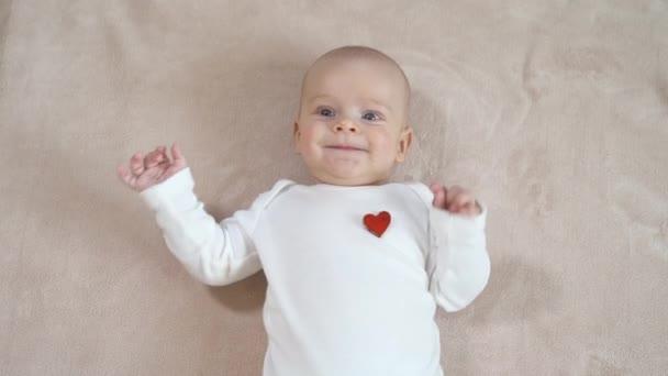Krásné dítě se usmívá. Velmi atraktivní dítě leží na přehozu a směje se. Detailní záběr