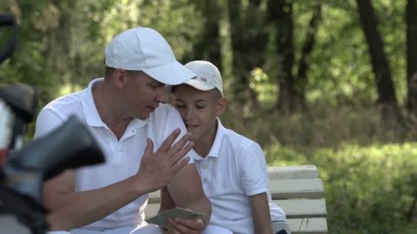 Šťastný muž s jeho syn golfisté chůzi na perfektní hřiště v letním dni