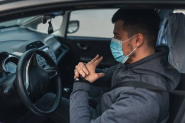 A man sits car and washes his hands with antiseptic gel. healthcare concept in car. The mask is white on the face. coronavirus, disease, infection, quarantine, covid-19