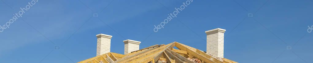 Roofing Construction. Wooden Roof Frame, White Chimneys and Yell