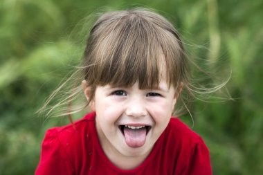 Smiling little girl shows tongue. Young cute little girl gesturi