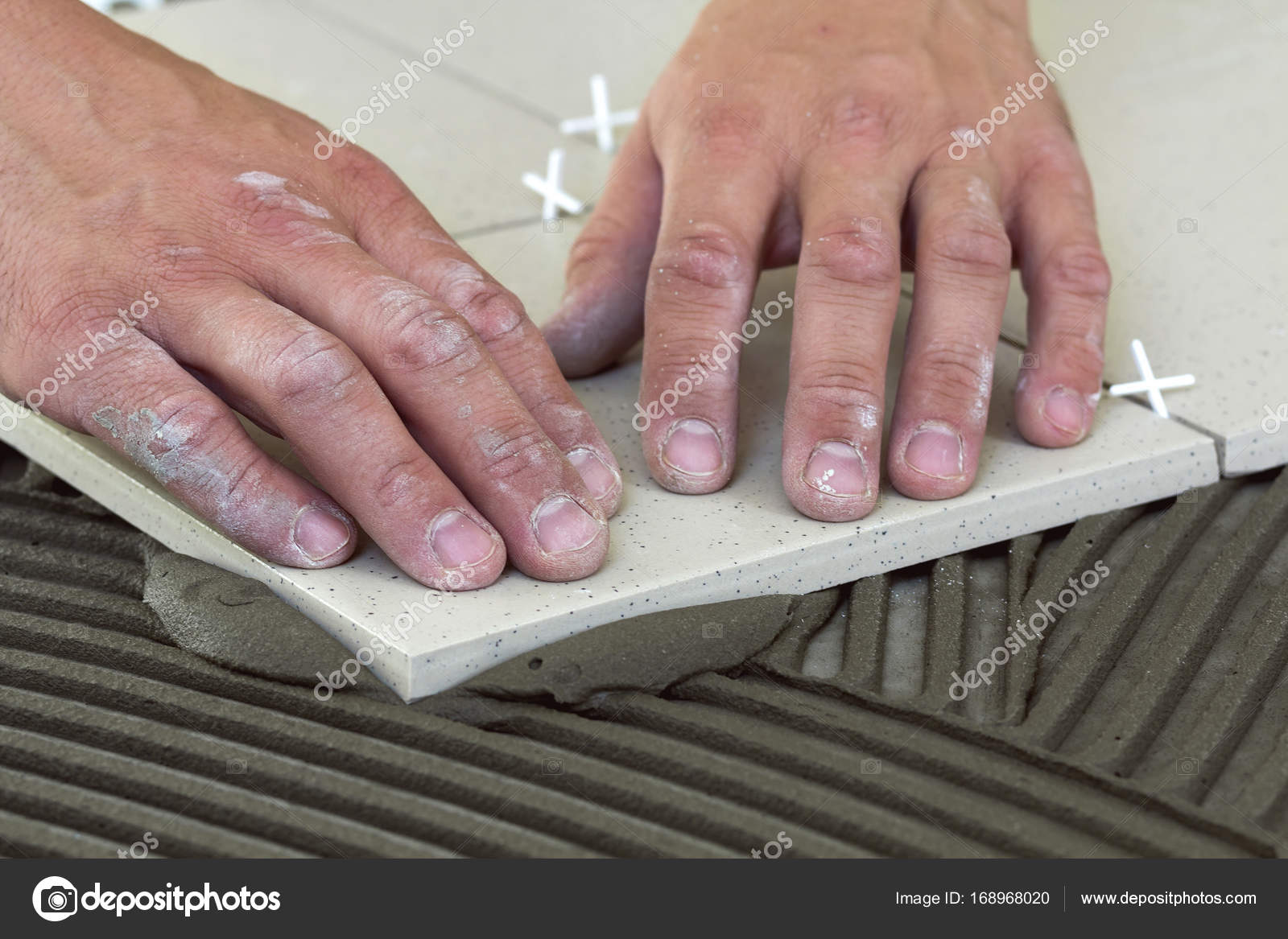 Workers Hands With Ceramic Tiles And Tools For Tiler Floor Tile