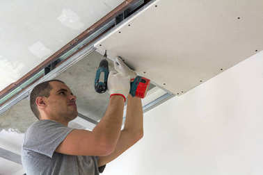 Construction worker assemble a suspended ceiling with drywall an