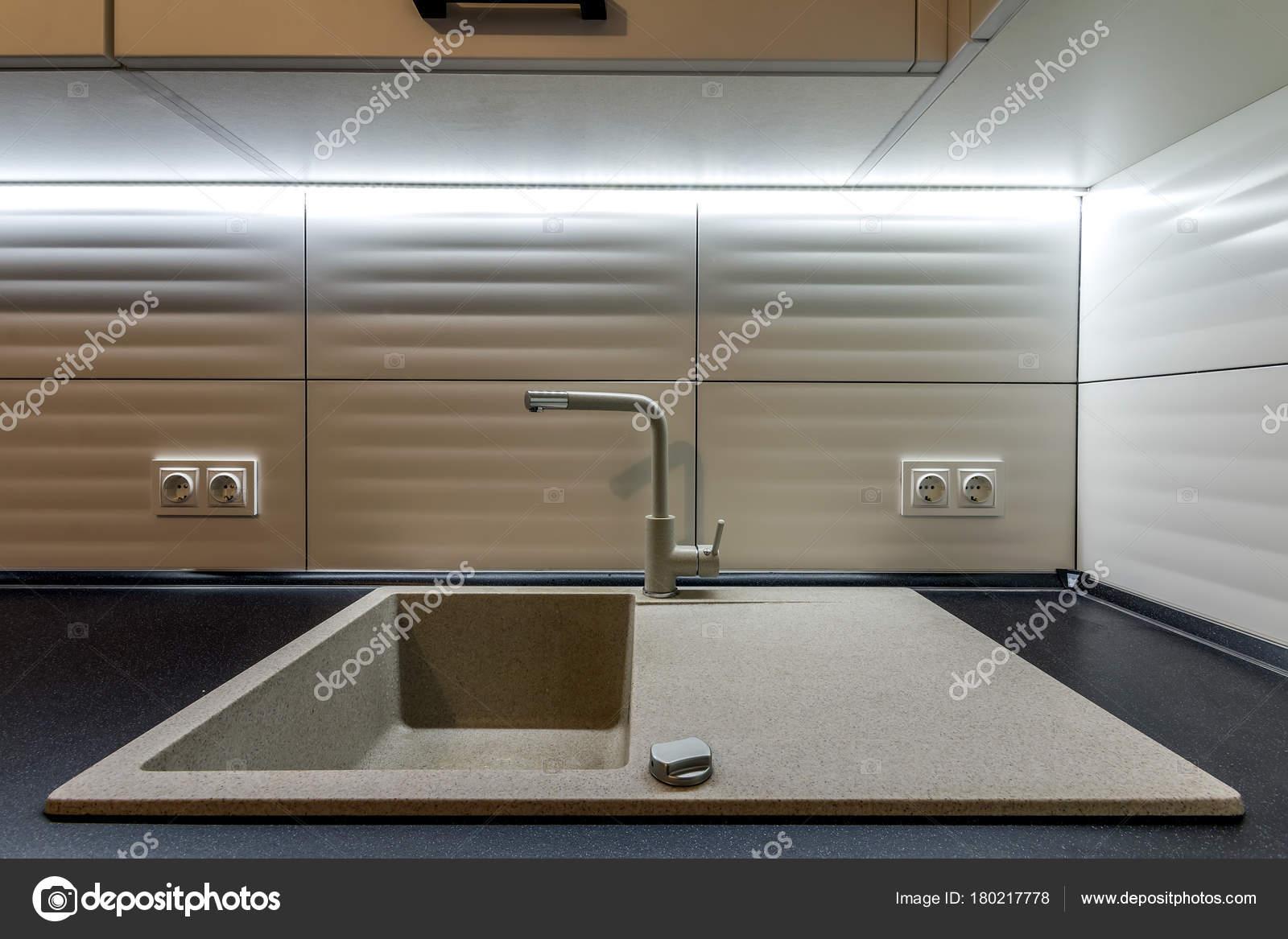 Granieten wasbak en water kraan in nieuwe moderne keuken interieur