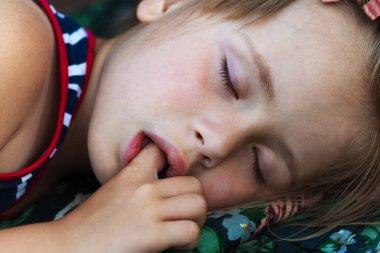 Portrait of sleeping pretty child girl who sucks her finger while sleeping.
