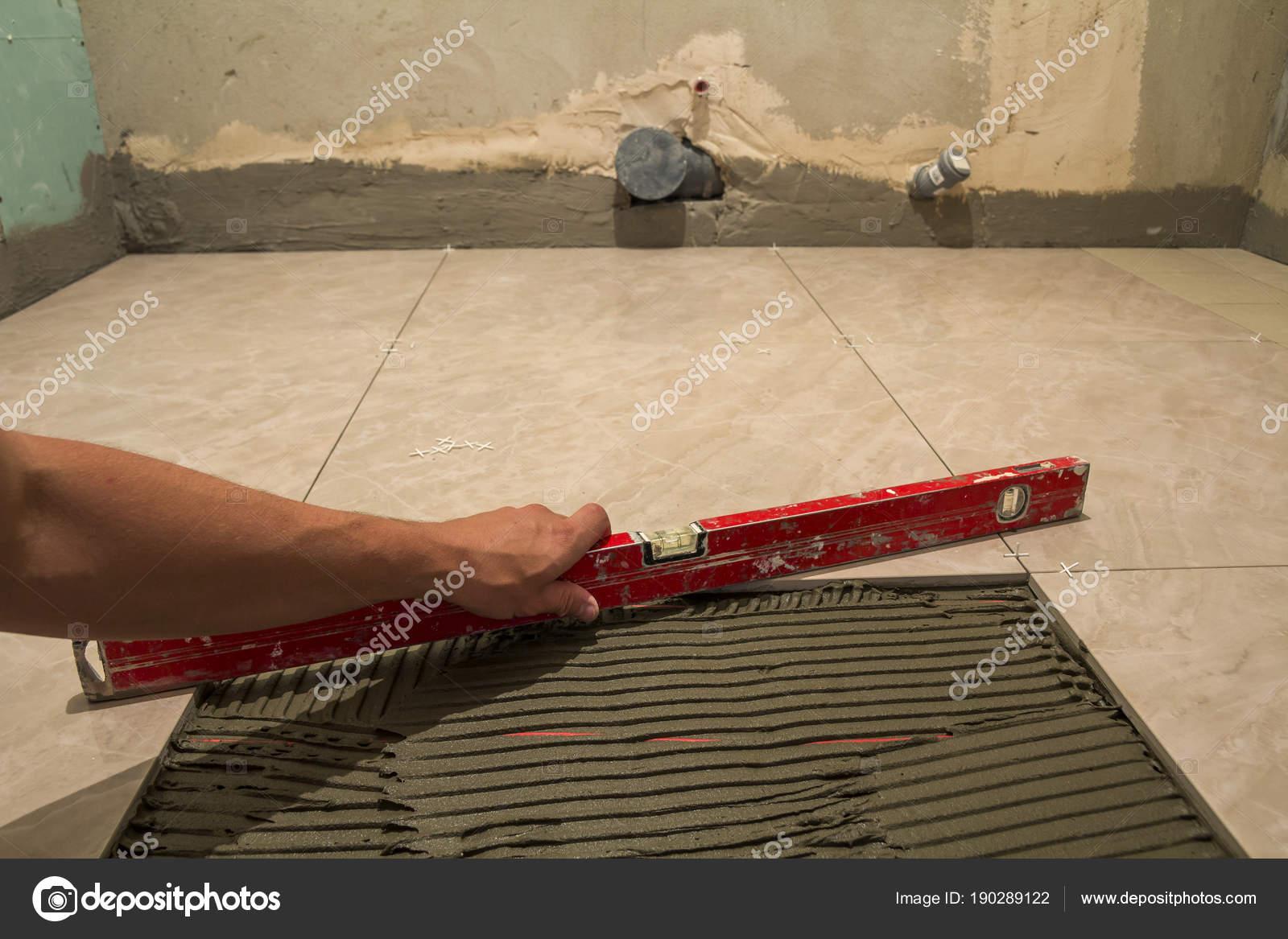 Fußboden Fliesen Renovieren ~ Keramische fliesen und werkzeuge für fliesenleger arbeiter hand